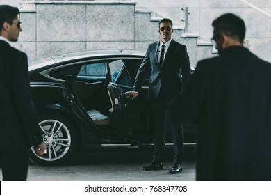 bodyguard in sunglasses opening car door to businessman