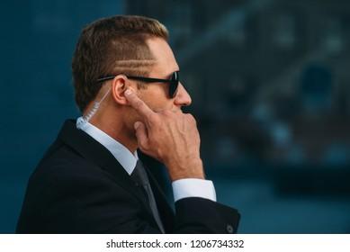 Bodyguard talking by earpiece, communication tools