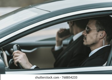 bodyguards with portable radio and security earpiece sitting in a car
