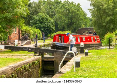 BODYMOOR HEATH, WARWICKSHIRE, UK - JUNE 25, 2017: Black Buck, a sixty foot narrow boat undertaking a cruise of the Black Country Ring, navigates the locks by the Dog & Doublet Inn at Bodymoor Heath.