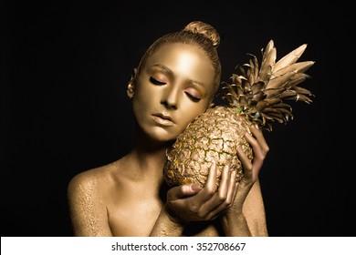 body-paint. gold bod-yart. beautiful sexy girl with fruit. golden makeup