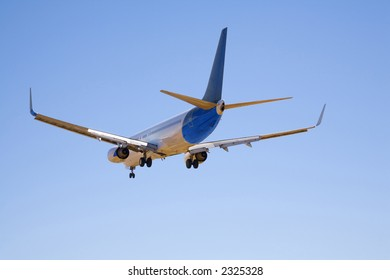 Boeing 737 in completely clear blue sky, with undercarriage and flaps down as it makes its final approach before landing. Seen from side rear.