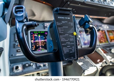 Boeing 737-800 Cockpit, March 2021, close-up of Boeing 737-800 control column with flight instruments and displays in the background. The checklist is located in the middle of control column