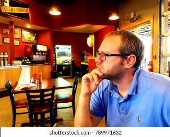 BOERNE, TX - AUGUST 11, 2017 -Young man with eyeglasses waits for order in restaurant.