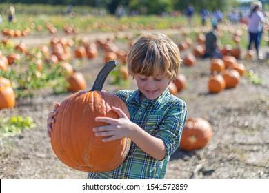 Bogart, GA / USA - 10/20/2019: Happy little boy holding pumpkin