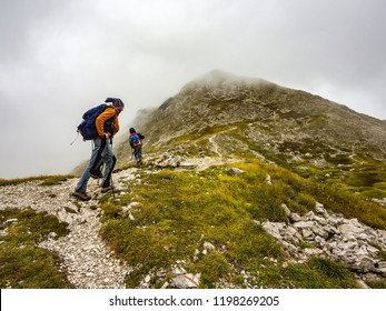 BOGATINSKO SEDLO, SLOVENIA - SEPTEMBER 23rd 2018: Mountaineers walking on the path from Bogatinsko sedlo to the top of the Bogatin ona a cloudy day autumn with some light rain and wind.
