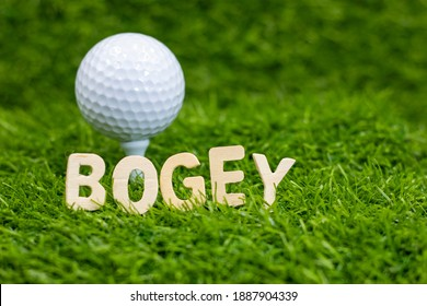 Bogey word with golf ball behind on green grass. one stroke over par a : one stroke over par on a hole made a bogey on the second hole - Shutterstock ID 1887904339
