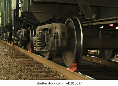 A bogie of freight railcar closeup, with brake shoe put under the wheel