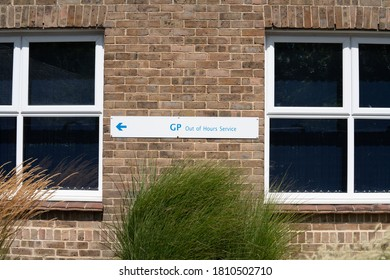 Bognor Regis, Sussex / UK - 1 Aug 2020: Sign for NHS GP Out of Hours service stuck on a red brick hall between windows. A left arrow and blue text on a white background. National Health Service, UK.