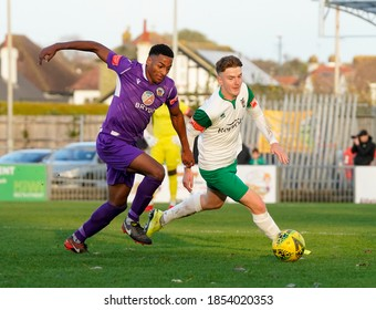 Bognor Regis, Sussex / UK - 31 Oct 2020: Soccer action from the Isthmian League 'Rocks' vs Tooting & Mitcham football club. Two players in green - white and purple strip tackle for the ball. High ISO.