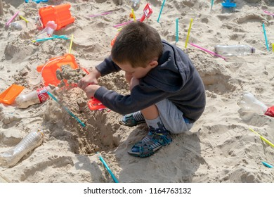 Bognor Regis, West Sussex / England - August 25 2018: Child plays in a sandpit using empty drink bottles, coloured plastic straws and plastic bucket and spade.