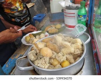 BOGOR, INDONESIA - November 24, 2016: Street food vendor selling siomay, Indonesian steamed fish dumpling with vegetables served in peanut sauce.