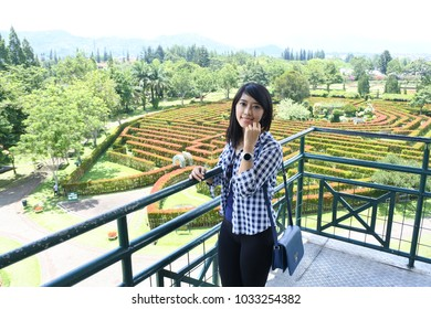 Bogor -November 6, 2017: a Java native sweet girl poses in the flower garden of Nusantara on November 6, 2017 in Puncak, Bogor, Indonesia