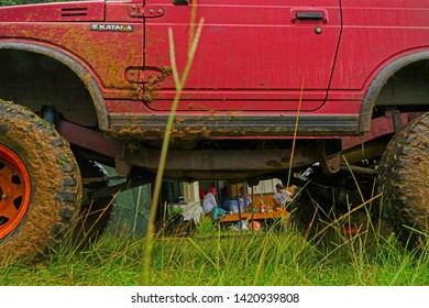 Bogor, West Java / Indonesia - January 2019: View of off road activity at a country involving all terrain cars captured after raining at muddy grassy route that makes participating cars dirty.