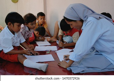 Bogor, West Java, Indonesia - July 2019 : A Catholic Nun from Ordo FMM (Franciscan Missionaries of Mary) teach children how to read and write.