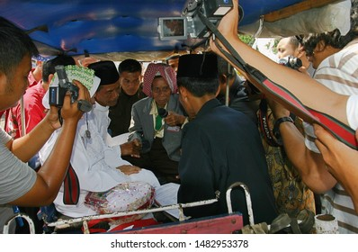 Bogor, West Java, Indonesia - March 2019 : Two videographers are documenting a wedding ceremony while some people are watching.