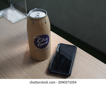 Bogor, West Java, Indonesia - September 12, 2021 - A refreshing drink of iced brown sugar coffee latte late by Chatime Indonesia on a wooden table with a mobile phone besides it. Selective focus.