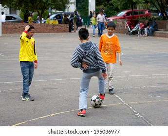 BOGOTA, COLOMBIA - APRIL 06, 2014: Young children playing soccer on pavement in a park in Bogota Colombia.