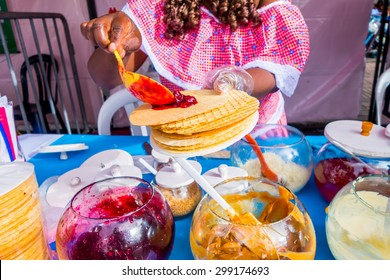 BOGOTA, COLOMBIA - FEBRUARY 25, 2015: Closeup traditional Colombian streetsnack oblea being prepared adding white sauce with top of jam and coco by lady on street in Bogota, Colombia