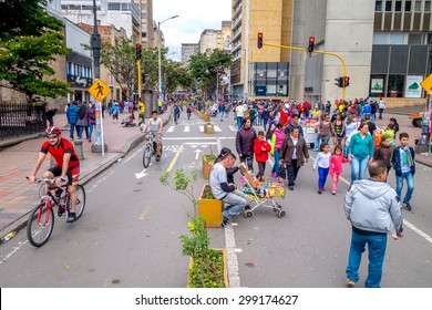 BOGOTA, COLOMBIA - FEBRUARY 9, 2015: Unidentified hispanic pedestrians and cyclists moving through city street Candelaria area Bogota