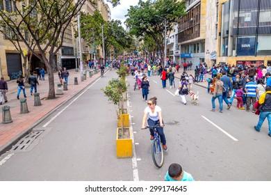 BOGOTA, COLOMBIA - FEBRUARY 9, 2015: Unidentified hispanic pedestrians and cyclists moving through city street Candelaria area Bogota