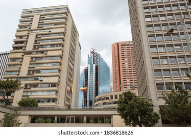 BOGOTA, COLOMBIA - OCTOBER 19 OF 2020  Two old office buildings with modern skyscraper and brick buildings with bogota and colombia flags scene in downtown city in grey cloudy day