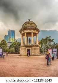 Bogota, Colombia - September 13, 2013: Estatua De Simon Bolivar at Parque de Los Periodistas, Journalists' Park in Bogota and high, modern, blue building. La Candelaria district of Bogota
