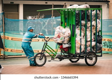 Bogota, Colombia - September 15, 2018: a garbage collector pulls a cart/car full of trash in the middle of the street. Downtown. La Septima