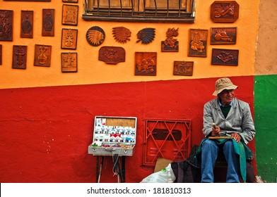 BOGOTA, COLOMBIA - SEPTEMBER 22: Man on a street corner selling art in Bogota, Colombia on September 22, 2010