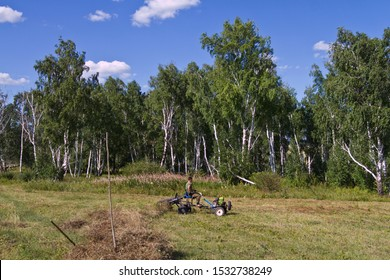 BOHAN, RUSSIA - AUGUST 12: Hay time - rural man mows grass on a mini tractor on August 12, 2018 in Bohan.
