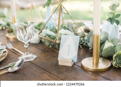 bohemian blue wedding table number on a wooden table, eucalyptus and gold decoration, watercolor style, bokeh background