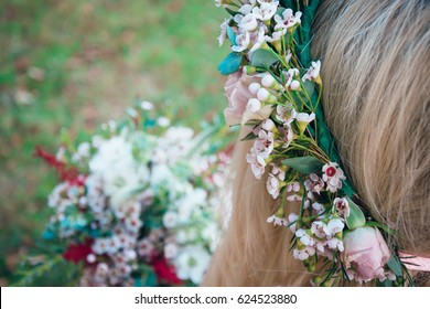 Bohemian bride showing off her beautiful boho flower bouquet. Elegant woman with stylish crown of pink spring flowers. Perfect image for: wedding, florist, magazine, website, fashion related subjects.