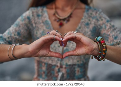 Bohemian chic gypsy woman wearing hands jewelry accessories and dress showing love sign. Boho detail close up