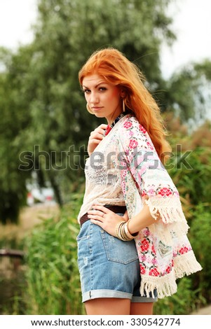 ef7121157a78 Bohemian fashion girl in kimono and blue denim shorts. Red haired young  woman in summer