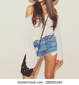 Bohemian fashion girl in white long sleeve blouse and blue denim shorts with crochet butterfly and black crochet purse. Brunette young woman in summer outfit.