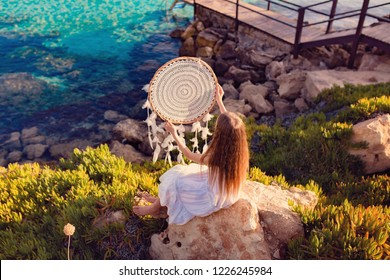 Bohemian girl with long red hair standing on the beach  holding dreamcatcher in white dress.