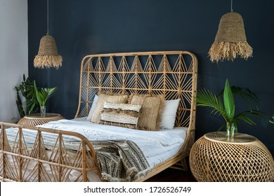 Bohemian style interior at cozy house with ethnic decor. Elegant bedroom with lamps over bedside tables, pillows at comfortable bed, cactus plant and copy space on deep blue wall