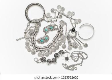 Bohemian style silver jewelry set on white background. Top view point.