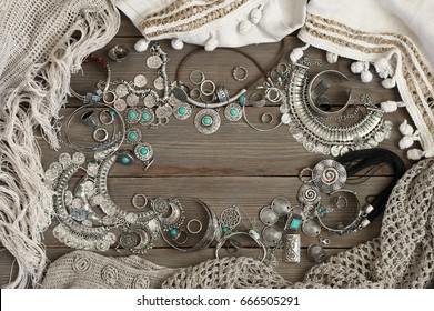 Bohemian style silver jewelry set and linen clothes on grey old wooden background. Boho outfit. Top view point.