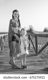 Bohemian vibe vacation. Full length portrait of smiling gypsy style mother and daughter outdoors in the summer evening on the beach