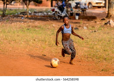 BOHICON, BENIN - JAN 11, 2017: Unidentified Beninese little boy plays football with bare feet. Soccer is very popular game among the  African kids