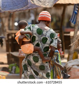BOHICON, BENIN - JAN 12, 2017: Unidentified Beninese woman in colored dress carries a baby from behind at the local market. Benin people suffer of poverty due to the bad economy.