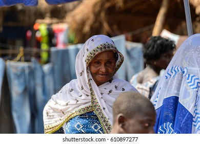 BOHICON, BENIN - JAN 12, 2017: Unidentified Beninese old woman in national clothes looks down at the local market. Benin people suffer of poverty due to the bad economy.