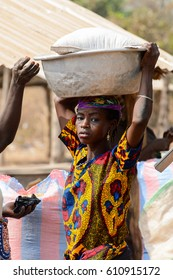 BOHICON, BENIN - JAN 12, 2017: Unidentified Beninese woman in colored dress carries a basin on her head at the local market. Benin people suffer of poverty due to the bad economy.