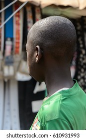BOHICON, BENIN - JAN 12, 2017: Unidentified Beninese boy in green shirt looks away at the local market. Benin children suffer of poverty due to the bad economy.