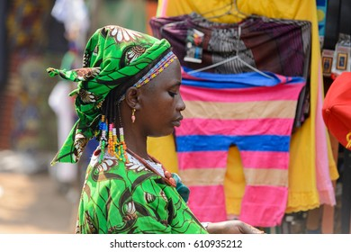 BOHICON, BENIN - JAN 12, 2017: Unidentified Beninese woman in green dress and headscarf looks down at the local market. Benin people suffer of poverty due to the bad economy.
