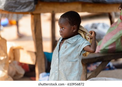 BOHICON, BENIN - JAN 12, 2017: Unidentified Beninese little girl in dirty clothes looks up at the local market. Benin children suffer of poverty due to the bad economy.