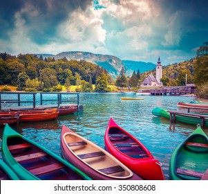 Bohinj Lake with boats and Church of St John the Baptist, Triglav National Park, Julian Alps, Slovenia. Instagram toning.