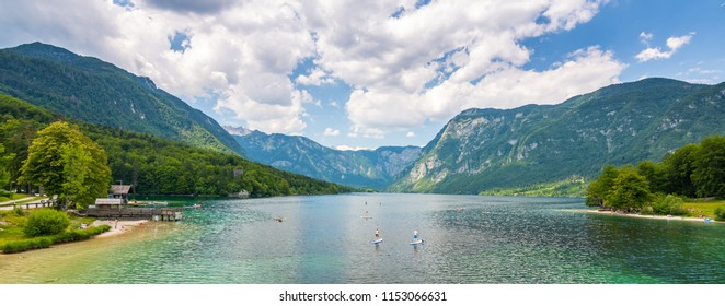 Bohinj Lake, Slovenia. Landscape of the lake with blue water and mountains in background. Slovenian alps and triglav mountain. Summer weather with clouds