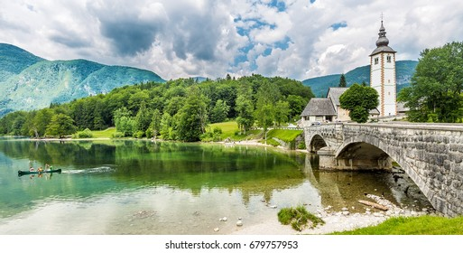 BOHINJ, SLOVENIA - JUNE 4, 2015: Church of St. John the Baptist and a bridge by the Bohinj lake, Slovenia.  The lake covers 318 hectares (790 acres) and is the largest permanent lake in Slovenia.